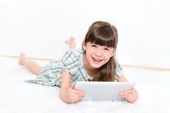Frohes kleines Mädchen mit Apfel ipad Lizenzfreies Stockfoto