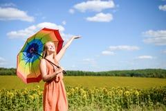 Frohes schönes Mädchen, das mehrfarbigen Regenschirm im Sonnenblumenfeld und im blauen Wolkenhimmelhintergrund hält Stockbilder