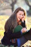 Frohes und lächelndes Mädchen, das ein Buch im Park liest Lizenzfreies Stockbild
