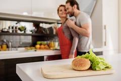 Frohes verheiratetes Paar, das im Kochraum umfasst Stockfotografie