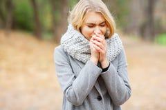 Froid et grippe La jeune femme dans un manteau gris marchant en parc d'automne et chauffe la main gelée photographie stock