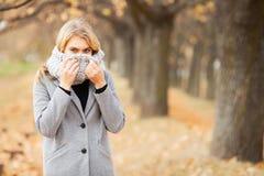 Froid et grippe La jeune femme dans un manteau gris marchant en parc d'automne et chauffe la main gelée images libres de droits