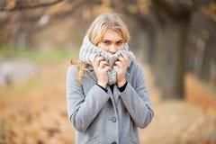 Froid et grippe La jeune femme dans un manteau gris marchant en parc d'automne et chauffe la main gelée image stock