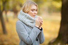 Froid et grippe La jeune femme dans un manteau gris marchant en parc d'automne et chauffe la main gelée photos libres de droits