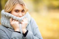 Froid et grippe La jeune femme dans un manteau gris marchant en parc d'automne et chauffe la main gelée photo stock