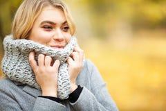 Froid et grippe La jeune femme dans un manteau gris marchant en parc d'automne et chauffe la main gelée photos stock