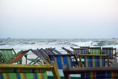 Froid sur la plage avec le lit du soleil de rayures Images stock
