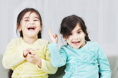Frolic sisters. Two little frolic sisters standing on green sofa Royalty Free Stock Images