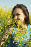 Frolicsome young girl in the middle  of yellow flowers Stock Photography
