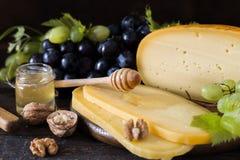 Fromage à pâte dure néerlandais Maasdam ou Emmental, fromage avec des trous et fromage de chèvre dur blanc Fromage entier, slisec photos stock