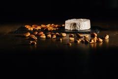 Fromage avec des écrous sur la table photos stock