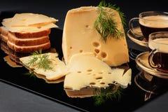 Fromage avec le fenouil, le pain blanc et deux tasses de café sur un fond noir Photos stock