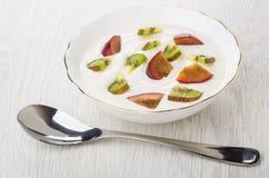 Fromage blanc avec des morceaux de kiwi et de prunes dans la cuvette Photos stock