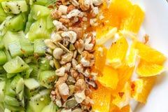 Fromage blanc et dessert crémeux avec l'orange, kiwi, écrous sur un fond rustique de paille image libre de droits