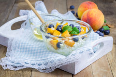 Fromage blanc frais avec la pêche, la myrtille, les amandes et le miel Photographie stock libre de droits
