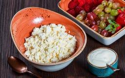 Fromage blanc frais avec les framboises, la fraise et les raisins juteux de baies sur le fond en bois foncé photographie stock libre de droits