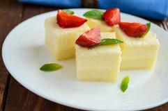 Fromage blanc sensible et soufflé crémeux sous forme de cubes, décorant des feuilles en bon état et des fraises fraîches image stock