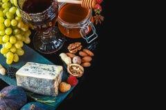 Fromage bleu de Dor avec des figues, des raisins, des écrous et le miel sur un panneau de schiste d'isolement sur un fond noir, c photo stock