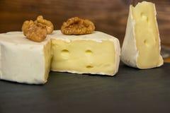 Fromage coupé en gros plan de camembert avec des écrous sur un fond foncé photo stock