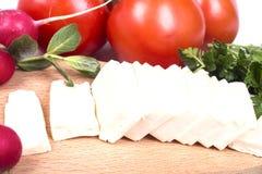 Fromage coupé en tranches avec des légumes Images stock