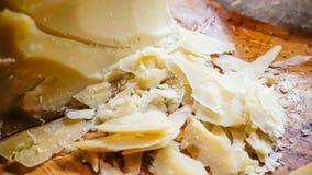 Fromage coupé en tranches de reggiano de parmesan sur le conseil en bois images stock