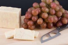 Fromage, couteau et raisins sur la planche à découper Image libre de droits