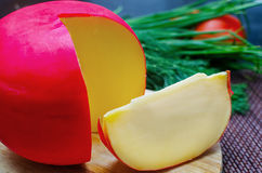 Fromage d'édam et un morceau sur la planche à découper Photo stock