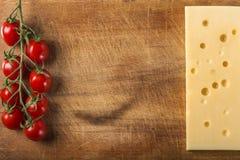 Fromage d'emmental avec le groupe de tomates-cerises sur le bois avec la copie Image stock