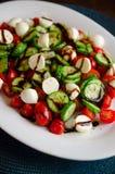 Fromage de Bocconcini avec des concombres et des tomates Photographie stock