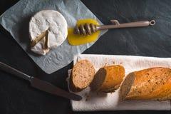 Fromage de brie, morceaux de la baguette, miel sur le parchemin Images stock