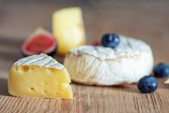 Fromage de camembert avec des figues et des myrtilles dessus sur le fond foncé photo libre de droits