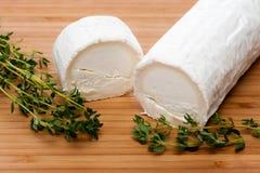 Fromage de chèvre avec le thym sur une planche à découper en bois Photographie stock libre de droits