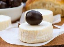 Fromage de chèvre avec les olives noires en bois Photographie stock libre de droits