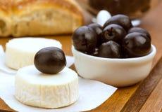 Fromage de chèvre avec les olives noires en bois Photos stock