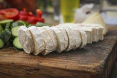 Fromage de chèvre français coupé en tranches sur la surface en bois Photos libres de droits