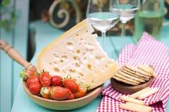 Fromage de Hollande avec les trous et la fraise Vin blanc en verre et casse-croûte Nourriture sur le balcon Vue de ci-avant Place photographie stock