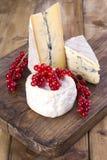 Fromage différent avec le moule blanc et bleu Baies fraîches d'une groseille rouge Fleurs blanches Fond et espace libre en bois p Image libre de droits