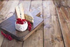 Fromage différent avec le moule blanc et bleu Baies fraîches d'une groseille rouge Fleurs blanches Fond et espace libre en bois p Photo libre de droits