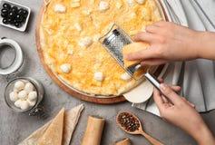 Fromage discordant de femme sur la pizza faite maison photographie stock libre de droits