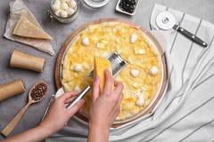 Fromage discordant de femme sur la pizza faite maison sur la table photographie stock