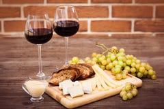 Fromage, pain brun grillé, deux verres de vin rouge Photos libres de droits