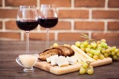 Fromage, pain brun grillé, deux verres de vin rouge Photo libre de droits
