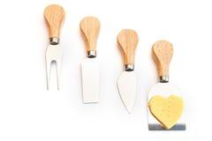 Fromage savoureux et couteaux d'isolement sur le blanc Photographie stock libre de droits