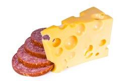 Fromage suisse avec des trous des parts d'un salami photographie stock