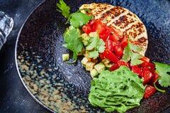 Fromage traditionnel cuit au four et grill? Halloumi de la Chypre avec la tomate et la sauce verte Salade faite maison fra?che su image libre de droits
