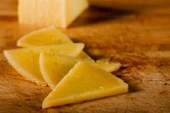 Fromage triangulaire sur le panneau en bois Photographie stock
