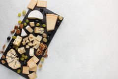 Fromages assortis avec des raisins blancs, noix, biscuits et sur un conseil en pierre Nourriture pendant une date romantique sur  images libres de droits