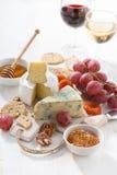 Fromages, fruit et casse-croûte moulés sur un fond en bois blanc Photos stock