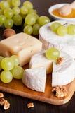Fromages, raisins et noix sur un fond en bois Images libres de droits