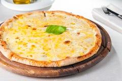 Fromaggi quattro Pizza des Käses vier auf einem rustikalen hölzernen Brett auf der gedienten Restauranttabelle Stockbild